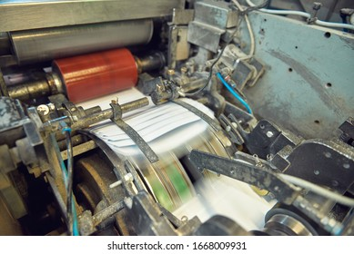 A industrial commercial envelope making machine, making paper envelopes for international distribution. Automated engineering machinery for mass production of paper envelopes.