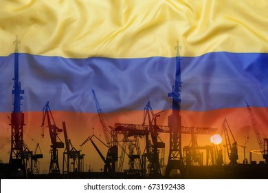 Industrial concept with Colombia flag at sunset, silhouette of container harbor