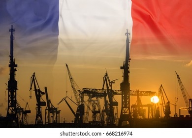 Industrial concept with France flag at sunset, silhouette of container harbor