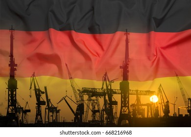 Industrial concept with Germany flag at sunset, silhouette of container harbor