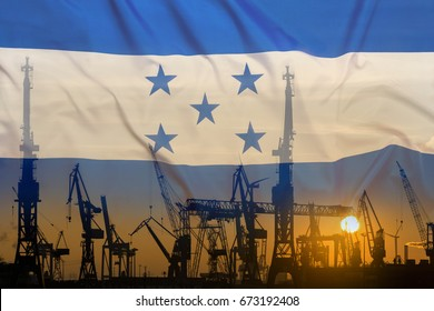 Industrial concept with Honduras flag at sunset, silhouette of container harbor