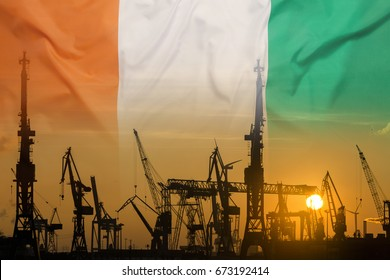 Industrial concept with Ivory Coast flag at sunset, silhouette of container harbor