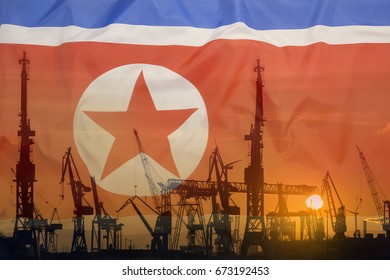 Industrial concept with North Korea flag at sunset, silhouette of container harbor