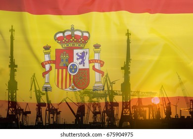 Industrial concept with Spain flag at sunset, silhouette of container harbor