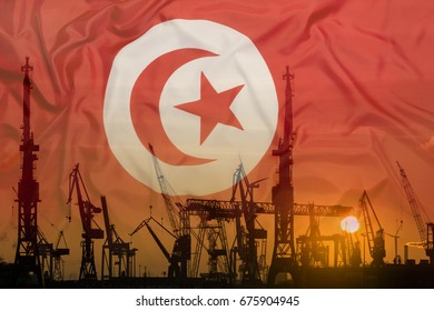 Industrial concept with Tunisia flag at sunset, silhouette of container harbor