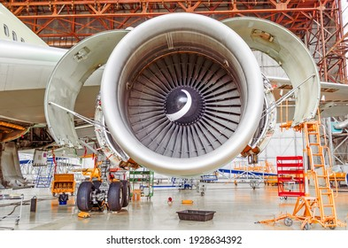 Industrial conceptual theme view. Repair and maintenance of aircraft engine with open hoods on the wing of the aircraft