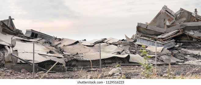 Industrial concrete building destructed by strike. Disaster scene full of debris, dust and crashed buildings.