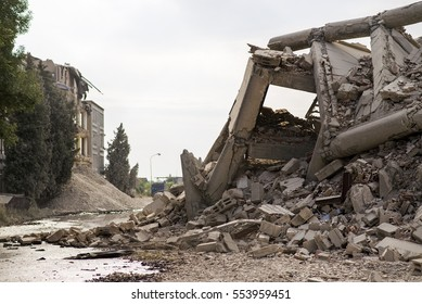 Industrial concrete building destructed by earthquake strike. Disaster scene full of debris, dust and crashed buildings.