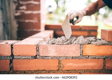 industrial Construction bricklayer worker building walls with bricks, mortar and putty knife