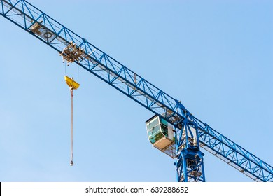 Industrial construction crane hoisting against blue sky.
