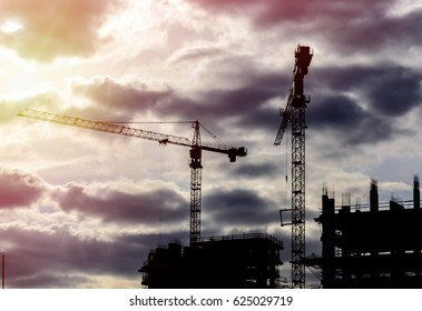 Industrial construction cranes and building silhouette at sunset.