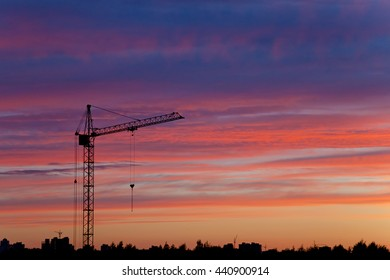 Industrial construction cranes and building silhouettes at sunset.