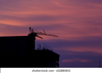 Industrial construction cranes and building silhouettes over cloud at evening