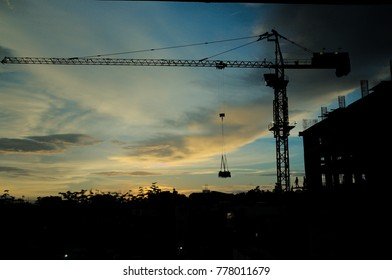 Industrial construction cranes and building silhouettes the blue sky