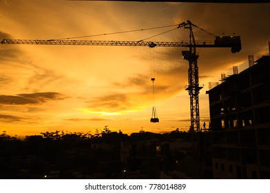 Industrial construction cranes and building silhouettes over sun at sunset