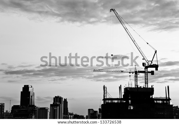 Industrial construction cranes and city silhouette over  sunrise. Processed in black and white.