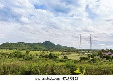 Industrial construction ,High Tension Wires in blue sky and green mountain in day light.