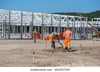 Industrial construction site of new commercial shopping mall. Workers in front, concrete piles foundation for the building, cranes and trucks in background. Ongoing framing, construction of factory