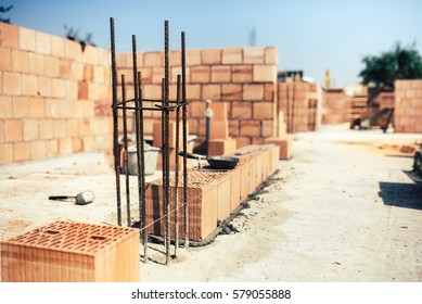 industrial construction site, placing bricks on cement while building exterior walls, industry details
