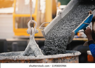 Industrial construction workers pouring wet concrete using concrete bucket