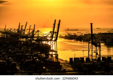 Industrial Container Cargo freight ship  with working crane bridge in shipyard at sunset