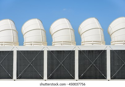Industrial cooling towers or air cooled chillers against blue sky