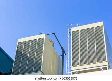 Industrial cooling towers or air cooled chillers on new building factory rooftop with blue sky background