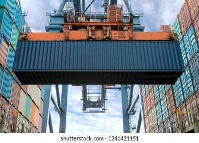 Industrial crane loading Containers in a Cargo freight ship. Container ship in import and export business logistic company. Industry and Transportation concept.