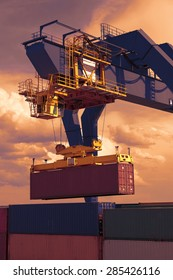 Industrial crane loading containers, sunset sky