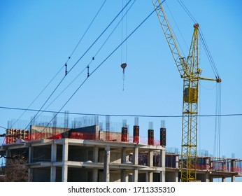 Industrial crane near building against blue sky. Construction site.