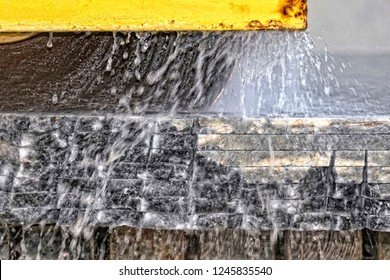 The industrial cutting factory marble cooled with water while being cutting. (Close-Up)