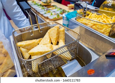 Industrial deep fryer closeup. Fast food restaurant equipment. Frying products in hot oil. Preparation of the fries. A quick side dish. The cook is going to cook nuggets on the deep fryer.