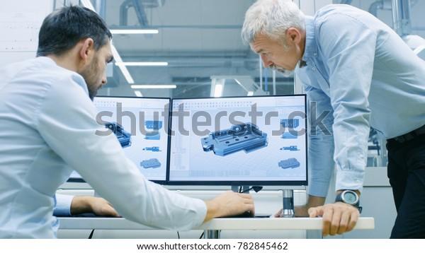Der Industriedesigner arbeitet mit Senior Engineer zusammen und entwirft neue Komponenten. Er arbeitet auf dem Personal Computer mit zwei Monitoren.