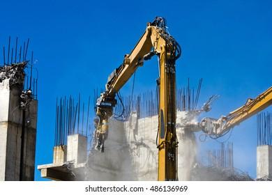 Industrial dismantle, mechanical destruction. Demolition crane dismantling a concrete building.