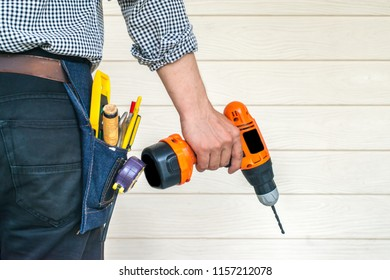 Industrial Drilling Equipment in Hand of Construction Worker. White copy space wall