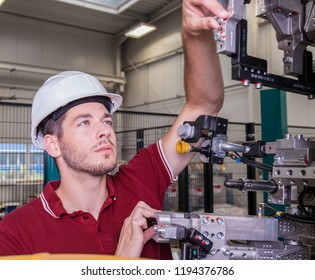 industrial engineer checks some joints of a robot in an automated welding shop of a car plant