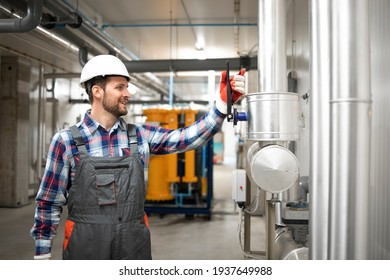 Industrial engineer closing valves of factory heating system at boiler's room to check gas installations. In background pipelines and electricity generator.