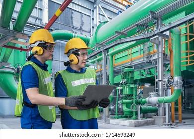 Der Industrieingenieur in Hard Hat verwendet Tablet während er in der Fabrik für Industrieproduktion steht. Hintergrund Öl- und Gasraffinerien. Zwei Werksarbeiter in einem harten Hut auf schwerem Gerät und Pipeline