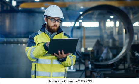 Industrial Engineer in Hard Hat Wearing Safety Jacket Uses Laptop. He Works in the Heavy Industry Manufacturing Factory with Various Metalworking Processes are in Progress.