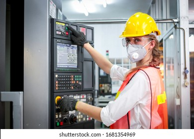 Industrial engineer worker female wearing helmet, safe glasses and mask, pointing and touching instrument panel buttons at manufacturing plant factory, young beautiful woman working in industry