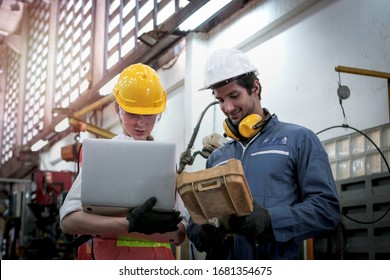 Industrial engineer worker woman and man wearing helmet discussing and working together at manufacturing plant factory, young people working in industry