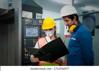 Industrial engineer worker woman and man wearing helmet, holding and looking at black file folder of document, discussing and working together at manufacturing plant factory, working in industry