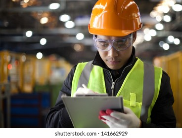 industrial engineer writing on notepad in factory
