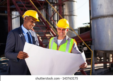 industrial engineers standing in front of a large oil refinery machinery with blueprint on hand