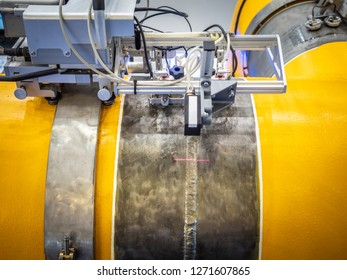 Industrial equipment. Welding pipes. The robot welds the pipe. Gas pipeline Automatic welding. Oil transfer. Yellow pipe.