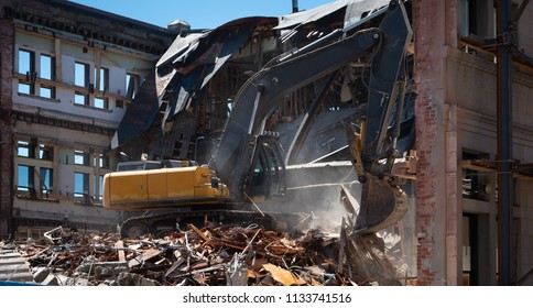 Industrial excavator demolishing old building making dust and debris.  Walls left standing showing windows and reinforcement bracing