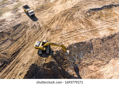 industrial excavator and dump truck prepare ground for future construction works. aerial photo