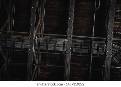 Industrial exposed ceiling with timber boards, steel beams and exposed wiring. Textured background graphic asset.