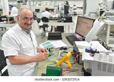 industrial factory for assembly of microelectronics - older, friendly worker at the workplace
