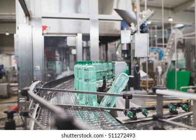 Industrial factory indoors and machinery. Robotic factory line for processing and bottling of pure spring water into canisters and bottles. Selective focus. Short depth of field.